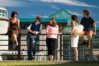 A picture of students leaning on a railing at the UNBC campus