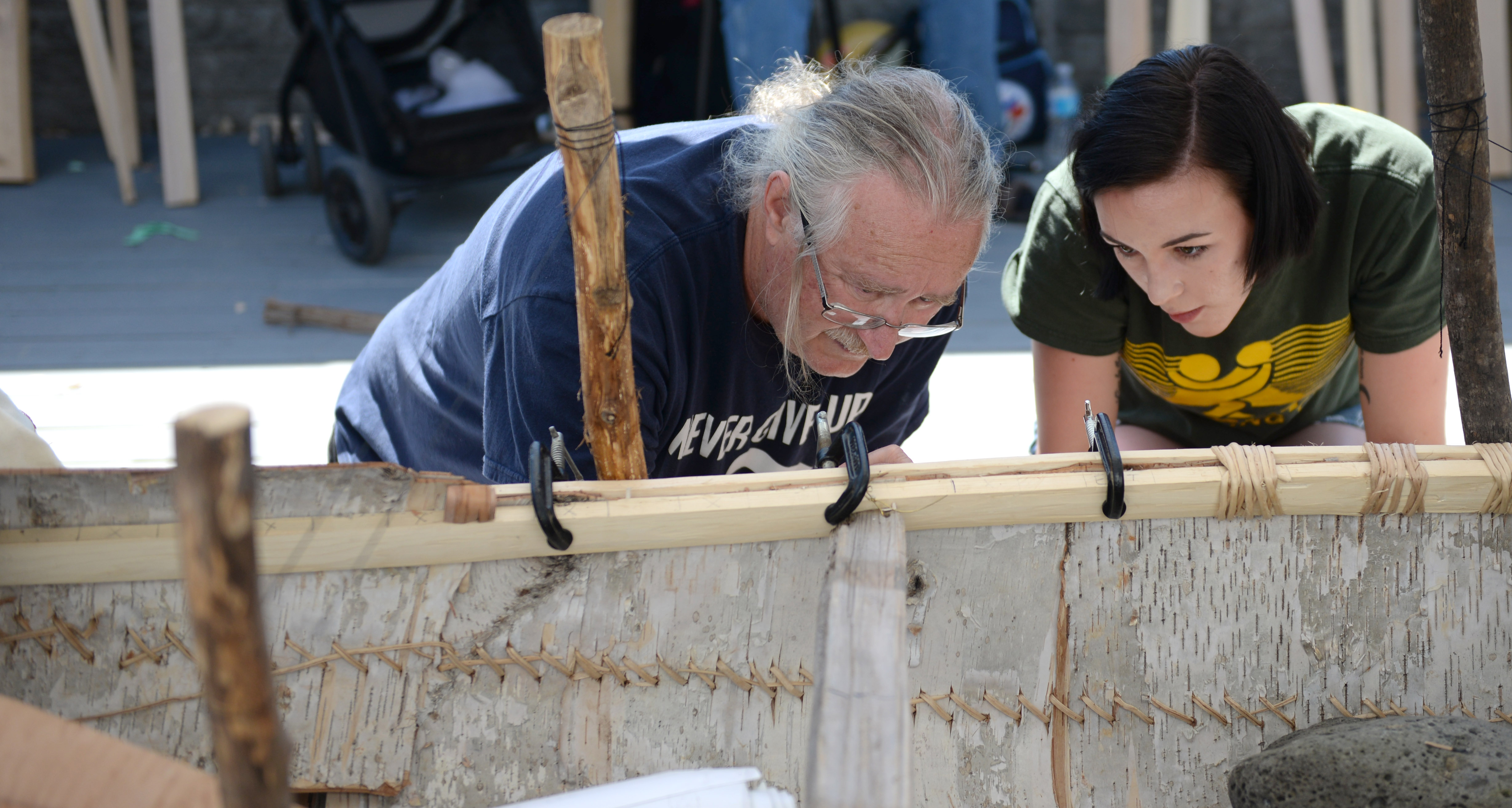 Instructor Marcel Labelle and student Karmyn Ziegler work on the canoe.