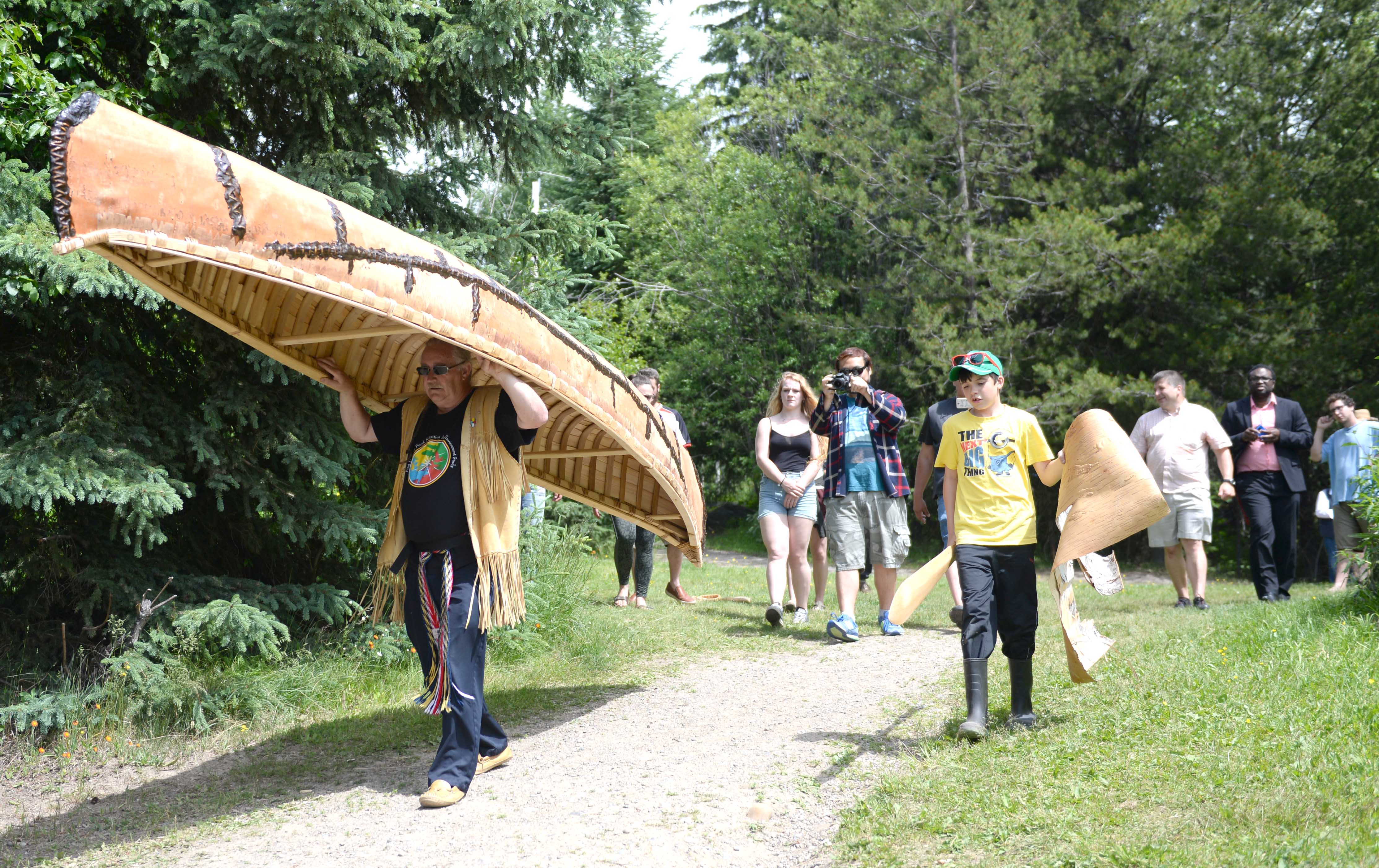 Instructor Marcel Labelle carries the canoe to the lake for the first time.