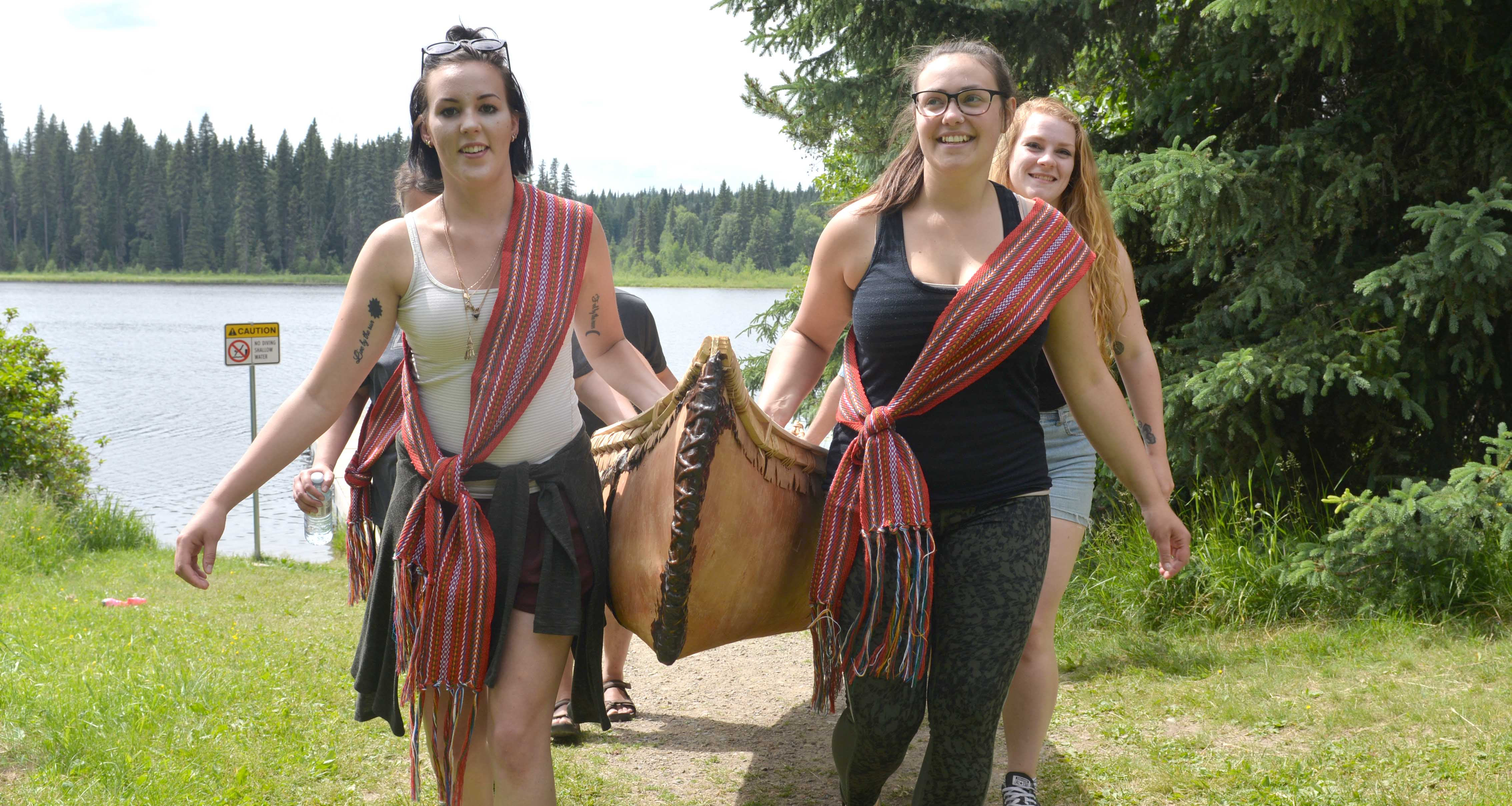 Students carry the canoe up from the water