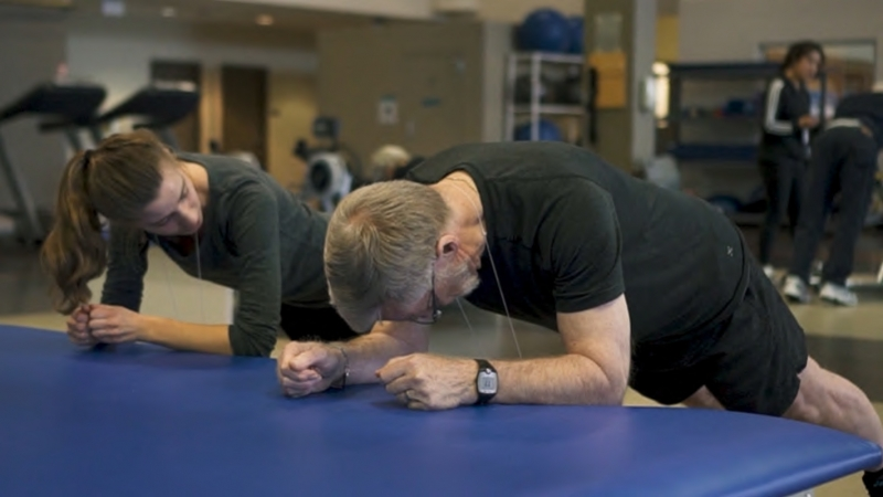Two people, one instructor and one person living with dementia, do forearm pushups in a gym.