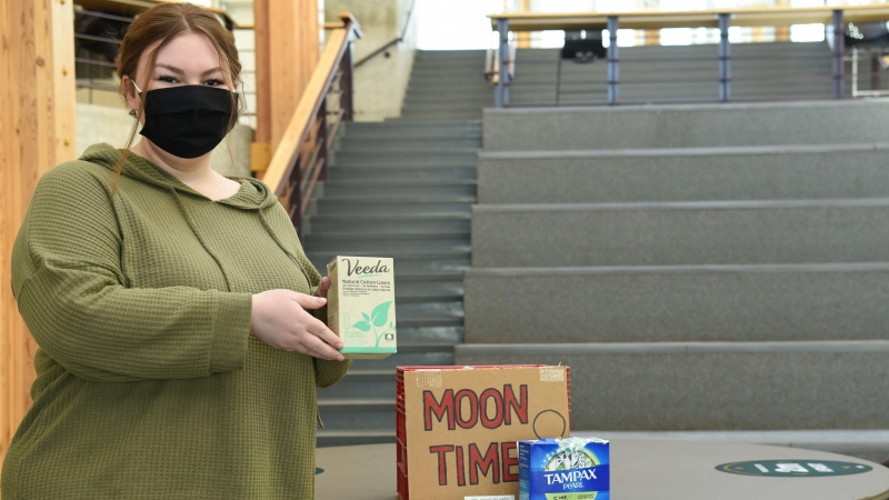 Social Work student Emily Erickson holds up menstrual products in the Canfor Winter Garden