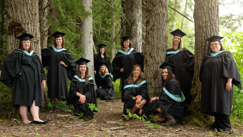 Terrace Education graduates posing in the forest on Ferry Island.
