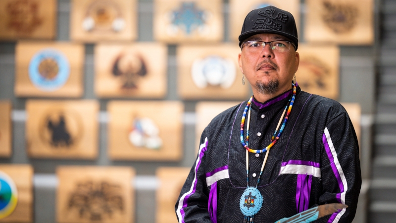 Artist Clayton Gauthier stands in the Canfor Winter Garden in front of 32 hand-carved cedar planks representing northern First Nations.