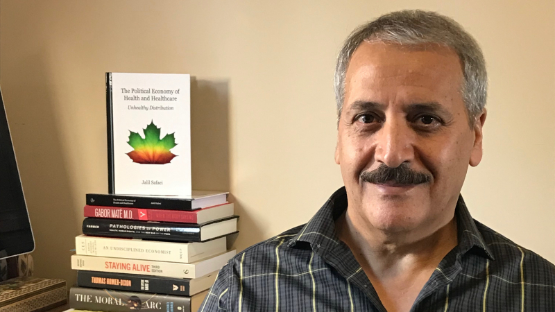 Economics Professor Dr. Jalil Safaei with his new book in the background