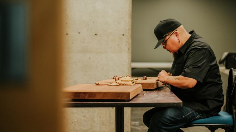Cree/Dakelh artist Clayton Gauthier carving designs on cedar planks.