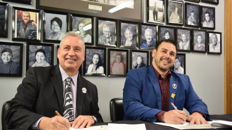 UNBC President Dr. Daniel Weeks and Lheidli T'enneh Nation chief Clay Pountney sign an Agreement.