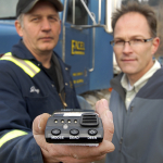Truck Driver from Excel Transportation and Roy Rea holding a GPS unit commissioned by the Prince George Wildlife Collision Reduction Committee to track live and dead roadside moose and deer.  These units are currently installed in the Northern Health Bus system (Diversified Transport) to track roadside wildlife locations for purposes of collision mitigation.