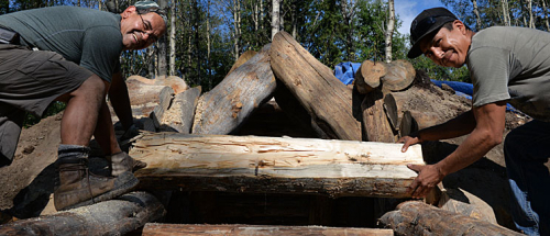 Course instructor Vince Prince, left, and Curtis Seymour place logs above the entrance of the pit house.