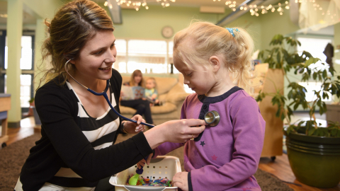 Nurse practitioner student Kristine Rowswell interacts with a child at daycare