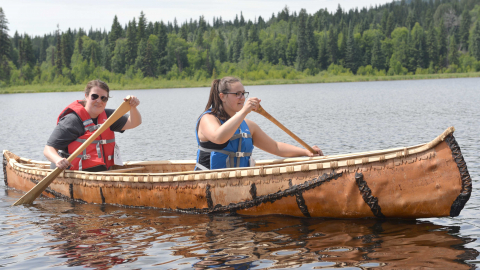 Students Nicole Hoffman and Jacey Wolfe paddle a birch bark canoe