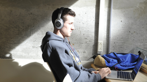 A UNBC student studies using a laptop and headphones